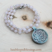 hypoallergenic om/lotus necklace with rose quartz, sterling silver & raku-fired ceramic focal